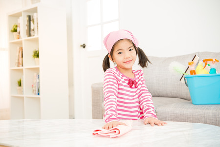 asian chinese cute little girl help make cleaning in the living room at home. housework and household concept.