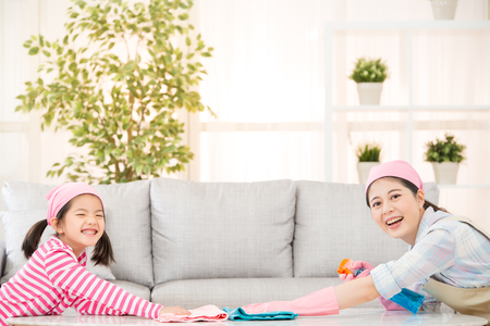 happy mother with kids spring cleaning room and having fun playing at home. A young woman and a little child girl dusting. family housework and household concept. Stockfoto