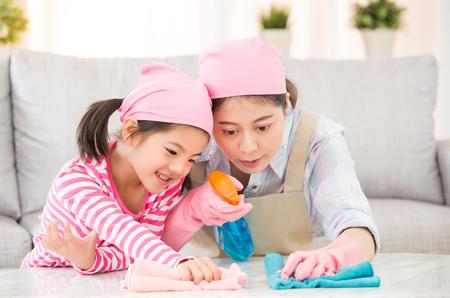 gemengd ras Aziatische Chinese moeder en dochter doen het schoonmaken in het huis. De gelukkige familie maakt de ruimte schoon. Een jonge vrouw en een klein kind meisje afstoffen. familie huishoudelijk werk en huishouden concept.