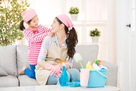 de gelukkige moeder voelt dochter zeer kinderlijke vroomheid die haar massage en huis het schoonmaken helpen die elkaar thuis in woonkamer kijken. huishoudelijk en huishoudelijk concept.