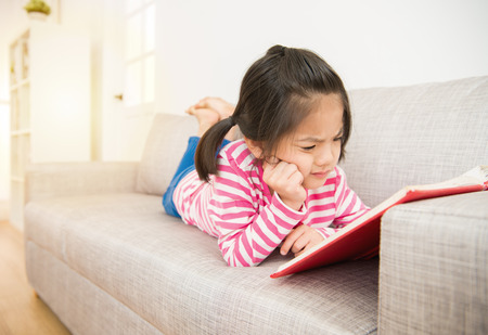 happy little asian chinese girl lying down on sofa reading story book feel hard and difficult to understand the content in the living room at home. family activity concept.
