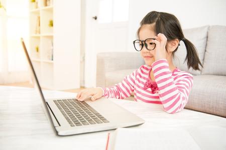 스마트 어린 아시아 중국 소녀 거실에서 그녀의 노트북 컴퓨터를 사용하는 동안 큰 안경을 착용. 가족 활동 개념입니다.