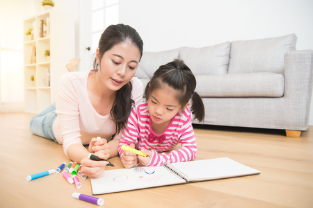 Mother and daughter are lying down on wooden floor having fun while drawing in the living room at home. family activity concept.