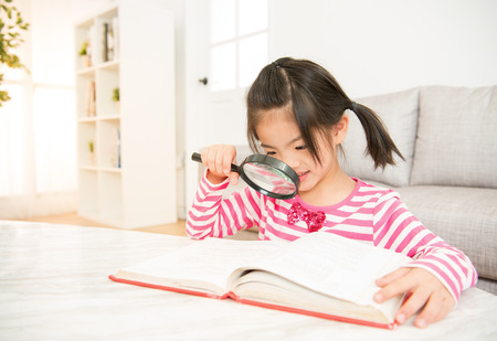 Little smiling asian chinese girl reading a book with a looking through magnifying glass. family activity concept.