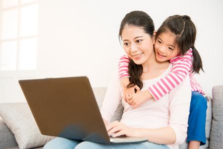 Bonne mère de relation et petite fille mignonne silhouette regardant l & # 39 ; ordinateur portable assis sur un canapé dans le salon à la maison. concept de l & # 39 ; activité de la famille Banque d'images - 80177053