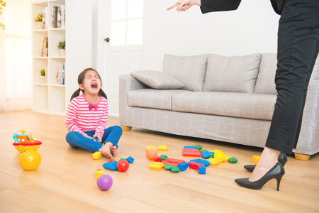 business woman back from office and see her daughter play toys messy up the living room feel angry and criticize the sadness asian kid girl at home. Stock Photo