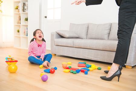 zakelijke vrouw terug van kantoor en zie haar dochter spelen rommelig speelgoed de woonkamer voelt boos en kritiek op de droefheid Aziatische jongen meisje thuis. Stockfoto