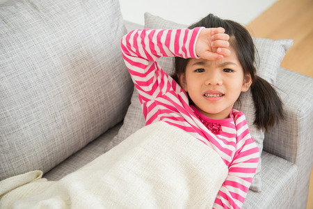 Little asian chinese girl with illness and hand on her head feel unwell on sofa in the living room at home. family activity concept. Imagens - 80250842