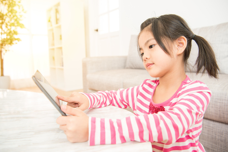 joy pad: beautiful kids girl having fun enjoy using digital tablet mobile pad at desk in the living room at home. family activity concept. Stock Photo