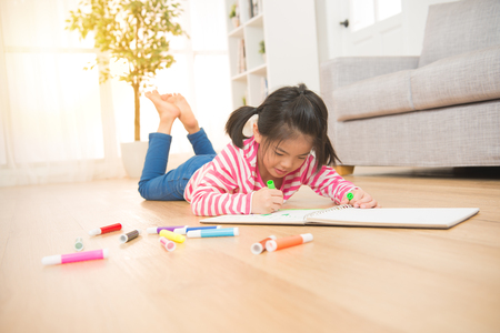 kids girl is concentrate drawing with felt-tip pen lying down on the wooden floor in the living room at home. family activity concept.