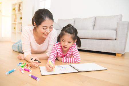 Gelukkige gemengde ras Aziatische moeder en dochter samen verf. volwassen vrouw helpt het kind meisje liggend op houten vloer tekening schetsboek in de woonkamer thuis. familie activiteit concept. Stockfoto