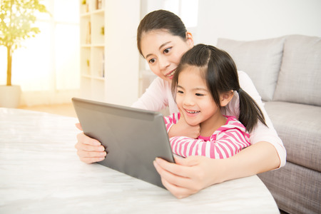 beautiful young mother and her cute daughter in shirts laughing and looking in digital tablet in the living room at home. family activity concept. Фото со стока - 80232563