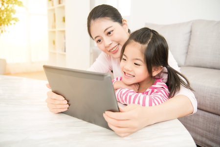 Beautiful asian chinese young woman and her charming little daughter are using a digital tablet and smiling while in the living room at home. family activity concept. Banco de Imagens