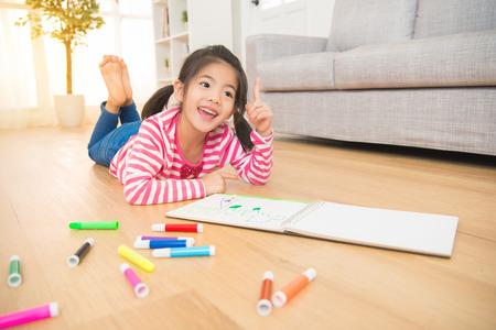 아이들은 꿈꾸며 스케치북 근처의 나무 바닥에 누워서 집에서 거실에 그림을 그리는 새로운 아이디어를 얻었습니다. 가족 활동 개념입니다. 스톡 콘텐츠