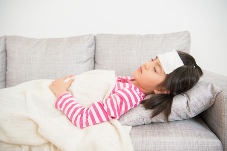 Young girl sleeping and sick with cooler gel on her head. and take care by his mom try to resting on sofa in the living room at home. family activity concept. Standard-Bild
