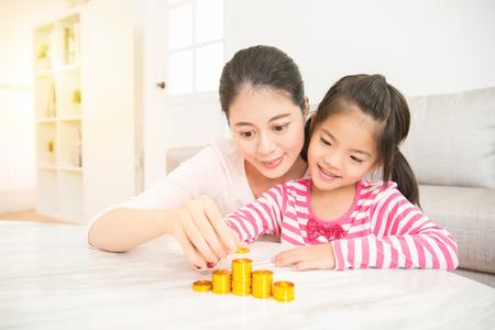 de gelukkige Aziatische moeder onderwijst haar dochter hoe te om geld in de woonkamer thuis te besparen en te berekenen thuis. familie activiteit concept.