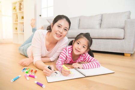 happy asian little girl painting drawing with her mother lying down on wooden floor drawing sketchbook in the living room at home. family activity concept.