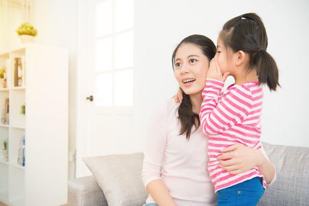 Glückliches nettes asiatisches Kindermädchen, das zu Hause das Geheimnis zu ihrer lachenden glücklichen Mutter im Ohr mit Spaßgesicht im Wohnzimmer flüstert. Familienaktivitätskonzept.
