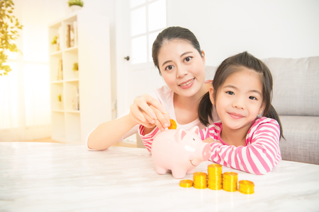 children saving money investment and happy family. people mother and daughter with small pink piggy bank in the living room at home. family activity concept.