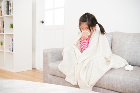 自宅のリビング ルームでソファの上に座って毛布でカバーしてティッシュで彼女の鼻を吹く少女病気。家族の活動のコンセプトです。