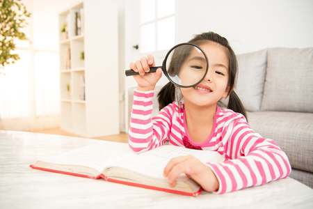 enlarger: Student little asian girl reading with magnifying glass looking at camera. sweet kids sitting in the living room at home. family activity concept.