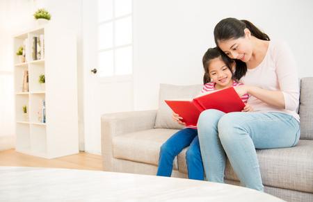 Heureuse mère chinoise asiatique et petite fille fille lisant un livre dans le matin ensemble dans le salon à la maison. concept de l & # 39 ; activité de la famille Banque d'images - 80232487