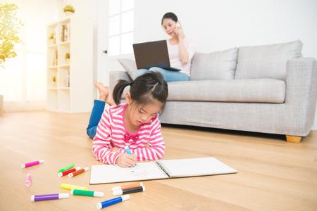 kinderen meisje liggend op houten vloer tekening op schetsboek en moeder werken met computer praten over de telefoon op de achtergrond in de woonkamer thuis. familie activiteit concept