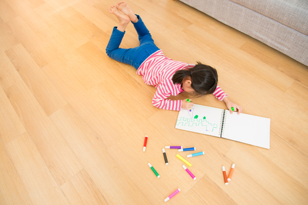 Top above view creative photo of little girl on wooden floor. Children lying down near sketchbooks and painting in the living room at home. family activity concept. Stock Photo
