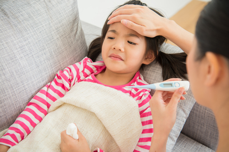 Cute little asian girl is ill lying on sofa bed mother checking a thermometer and touching daughter's forehead in the living room at home. family activity concept.