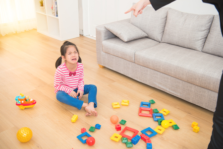 long day working businesswoman back from office feel shocked and angry criticize her sad crying little girl mess up all over of living room sitting on wooden floor at home. Stock Photo