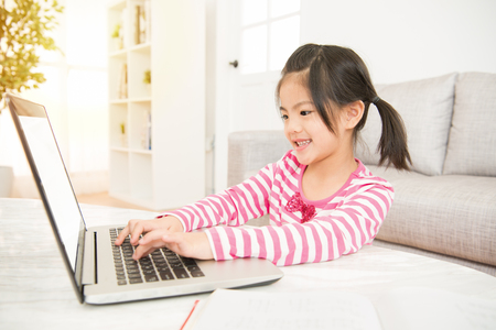 glad little asian schoolgirl with her computer at the table in the living room at home. family activity concept.