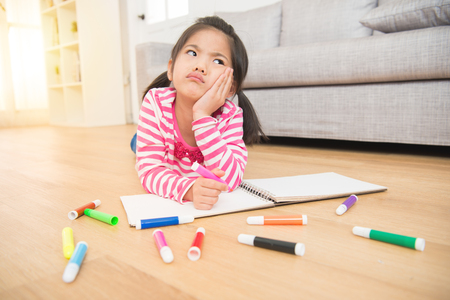 depressed child girl drawing with colorful pen in album using a lot of tools and lying down on wooden floor in the living room at home. family activity concept.
