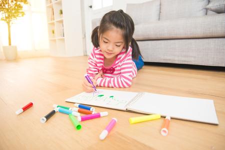 Aziatische chinese mooie meisje is tekenen met viltstift liggend op de houten vloer in de woonkamer thuis. familie activiteit concept.