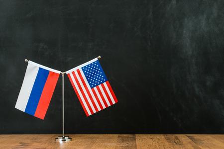 Amerikaanse en Russische vlag op vlaggenmast internationale bedrijfssamenwerking samen voor zwart bord met exemplaarruimte.