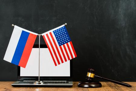 adjudgement van de VS en Rusland internationale kwestie met houten rechter hamer en vlag op vlaggenmast voor schoolbord krijtbord met kopie ruimte.