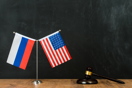 judgment of Russian and American political problem with judge hammer and flag on flagpole in front of blackboard chalkboard with copy space.