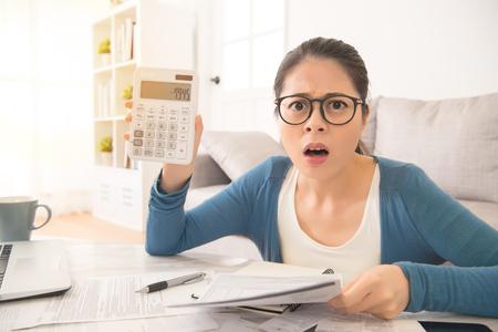 Die entsetzte Frau, die teuren Strom und Haushaltsrechnungen zählt, fühlt sich entsetzt, nachdem die Zahlen auf Sofa im Wohnzimmer zu Hause sitzen. Innen- und Hausarbeitskonzept.