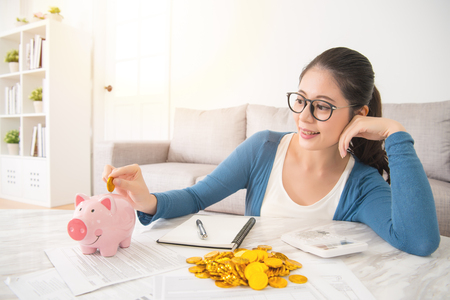 young mixed race asian woman deposit gold coin into piggy bank for future life sitting on sofa drinking coffee in the living room at home. interior and domestic housework concept. Archivio Fotografico