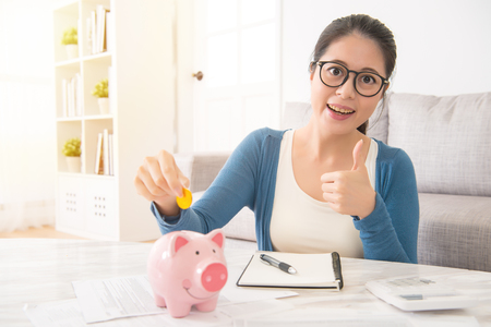 happy asian girl student with holding money savings into piggy bank for the college scholarship showing thumb up sitting on sofa in the living room at home. interior and domestic housework concept.