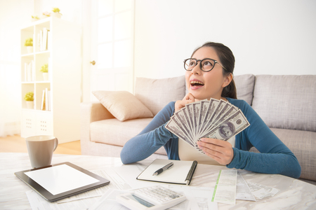 Closeup portrait happy excited successful young student girl holding money dollar bills in hand looking up dreaming. Positive emotion facial expression feeling. Financial reward