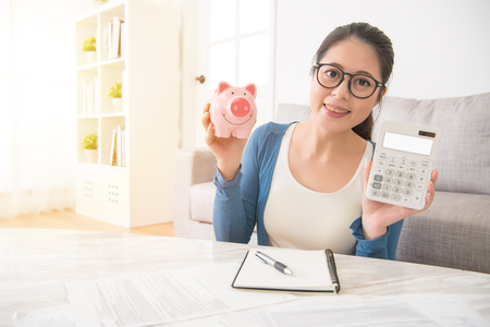 joyful Chinese Asian woman hold piggy toy and calculator starting to plan saving money dollar soon and successful