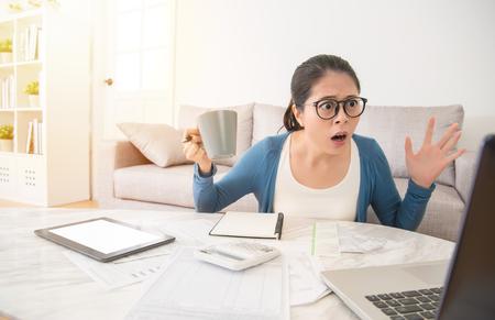 自宅の居間でソファーに座っていた国内の財政法案を議論してショックを受けたアジア中国の主婦を心配しています。インテリアと国内の家事の概 写真素材