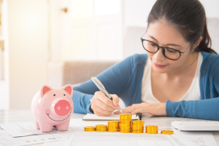 piggy bank money tower in front of happy asian chinese house woman counting and recording her savings sitting on sofa in the living room at home. indoors interior and domestic housework.