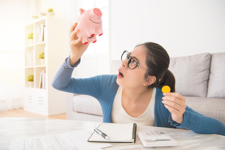 young unhappy woman emptying her piggybank savings with less than expected sitting on sofa in the living room at home. interior and domestic housework concept.