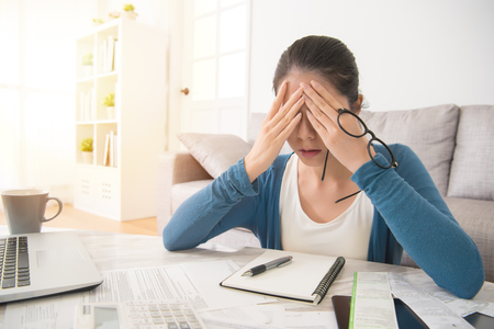 depressed young mixed race asian woman use hands cover her face after checking bills and bank account balance sitting on sofa in the living room at home. interior and domestic housework concept.