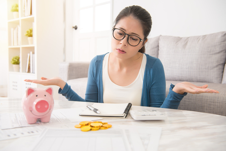 helpless young asian chinese woman having financial problems sitting on sofa in the living room at home. interior and domestic housework concept. Stock Photo - 80442459