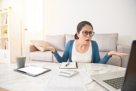 helpless young asian chinese woman checking computer laptop and having financial problems sitting on sofa in the living room at home. interior and domestic housework concept.
