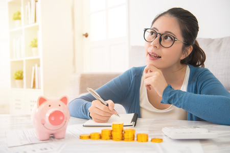happy asian chinese house woman dreaming and recording writing her savings from piggy bank money tower sitting on sofa in the living room at home. indoors interior and domestic housework.