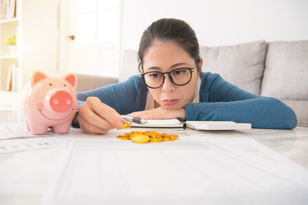Chinese Asian young woman lie on the desk and upset counting money coin sitting on sofa in the living room at home. indoors interior and domestic housework. Stock fotó