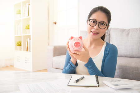 Glasses eyewear savings piggybank. Woman happy excited over saving money buying glasses. Young beautiful Chinese Asian woman. interior and domestic housework concept.